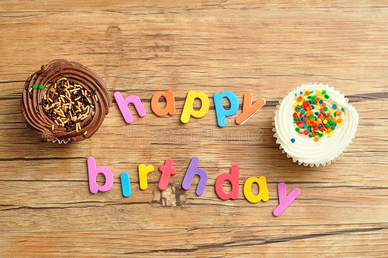 Happy birthday in colorful letters with a white cupcake and a chocolate cupcake royalty free stock photography