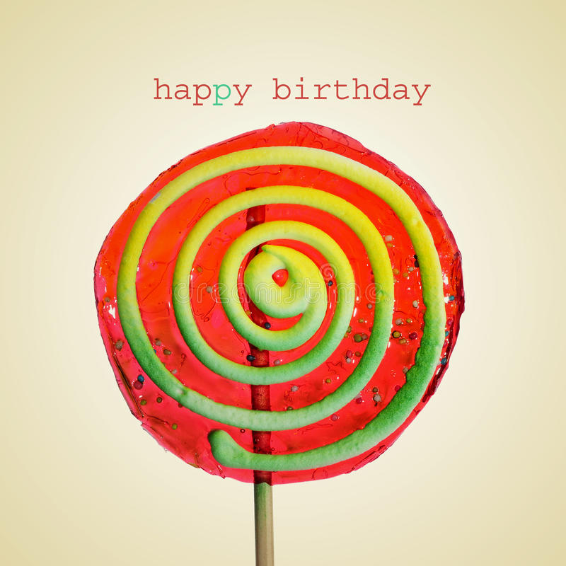 Happy birthday. A colorful lollipop with a spiral pattern with the text happy birthday on a beige background, with a retro effect stock photos