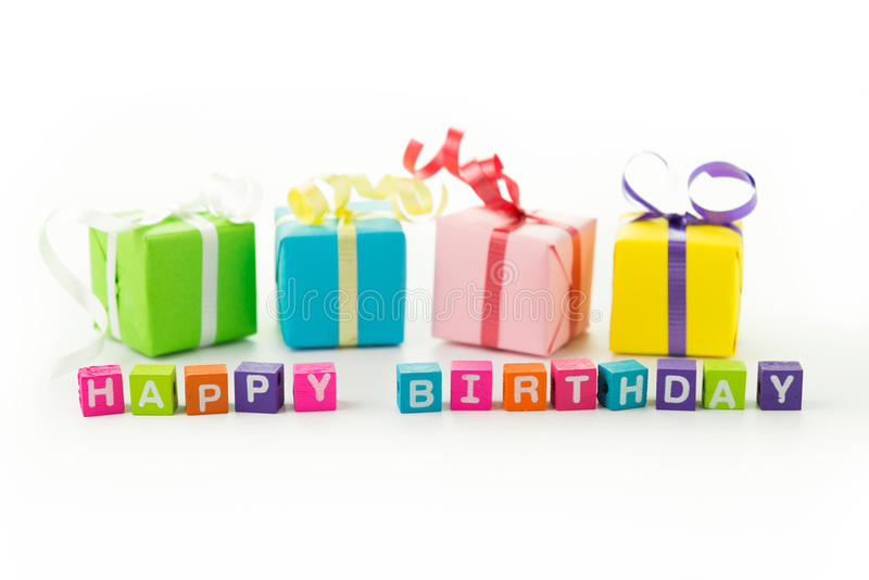 Happy birthday. Colourful happy birthday message and gift boxes on white background royalty free stock images