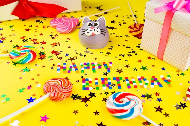 Concept happy birthday. Happy birthday concept with copy space, cake, gifts and caramel for birthday on yellow background stock images