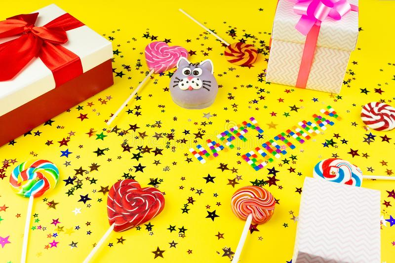 Concept happy birthday. Happy birthday concept with copy space, cake, gifts and caramel for birthday on yellow background royalty free stock image