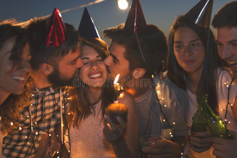 Happy birthday. Couple of young friends having a birthday party, singing a song and kissing a birthday girl. Focus on the birthday girl and two guys kissing her stock photo