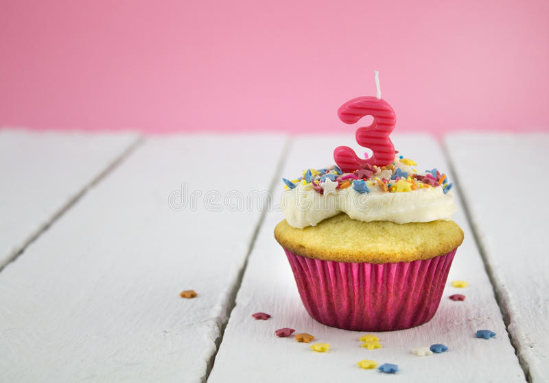 Happy birthday cup cake with star sprinkles and number 3 pink ca stock photos