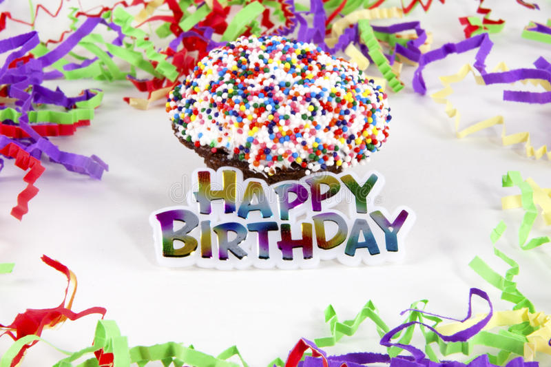 Happy Birthday Cupcake. Happy Birthday sign in front of decorated cupcake surrounded by colorful streamers royalty free stock image