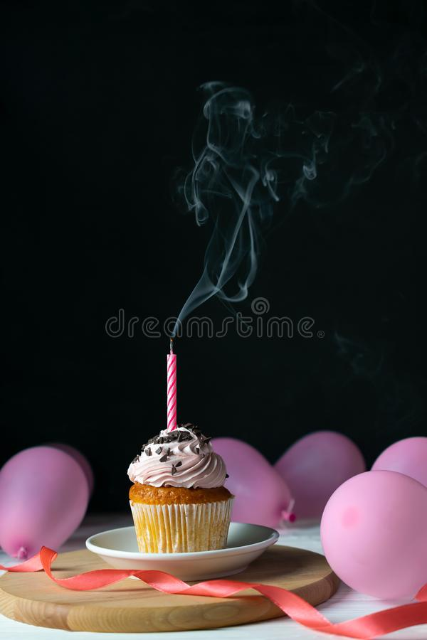 Happy birthday cupcake with a candle blown out on a black background with balloons royalty free stock photos