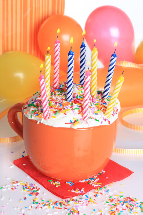 Happy birthday cupcake and candles. Happy birthday cup cake with lit candles and balloons royalty free stock photo