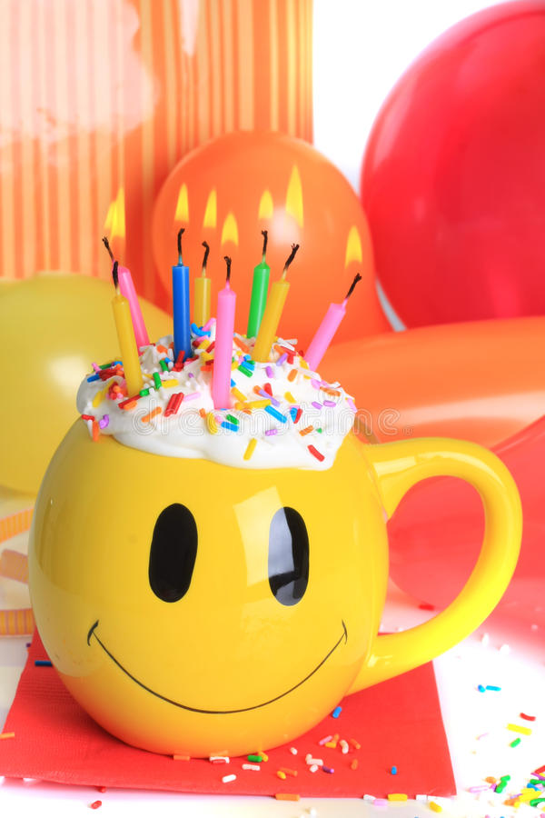 Happy birthday cupcake and candles. Happy birthday smiley face cup cake with lit candles and balloons royalty free stock images