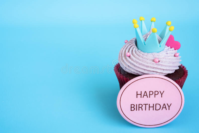 Happy birthday cupcake with crown and pink heart over blue background. With copy space, Gift for birthday royalty free stock photos