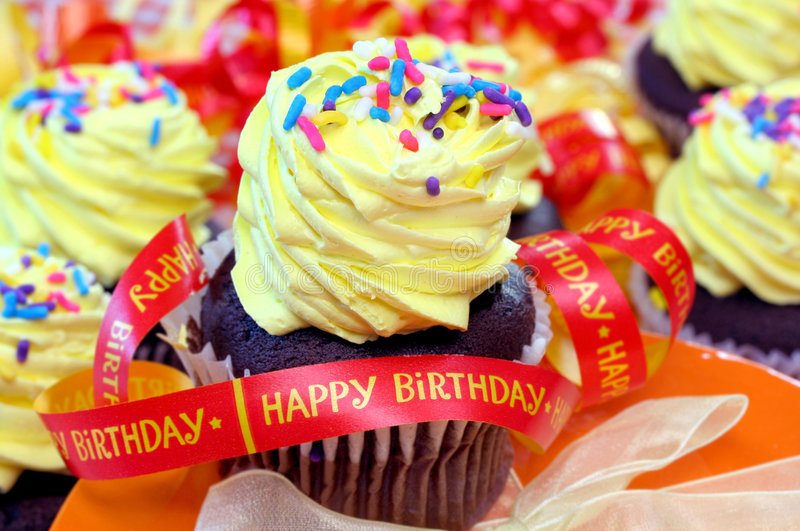Happy Birthday Cupcakes. Yellow frosted cupcakes with orange Happy Birthday ribbon. Festive and vibrant colors royalty free stock photos