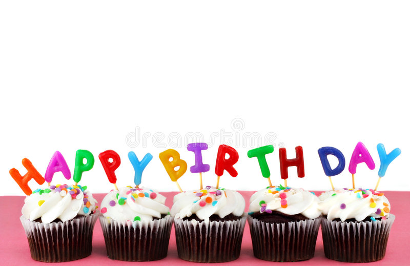 Happy Birthday Cupcakes with candles. Cupcakes in a row with Happy Birthday candles on top. Background is white with copy space stock photo