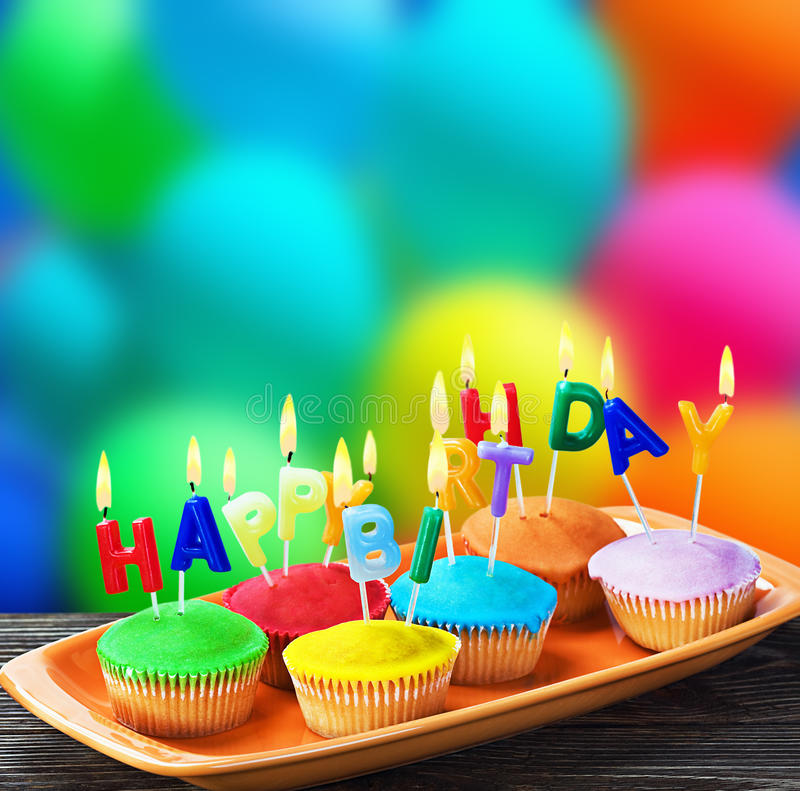 Happy birthday cupcakes with candles. Colorful happy birthday cupcakes with candles royalty free stock images