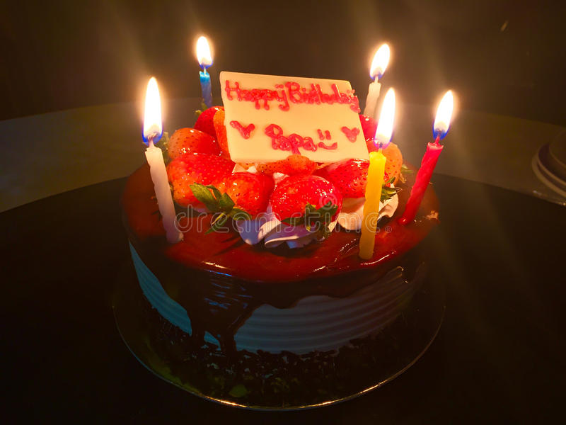 Happy Birthday Dad. Strawberry Cake with Candle Light in the Dar. K stock photography