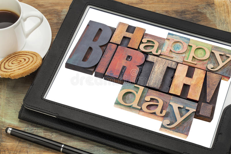 Happy birthday on digital tablet. Happy birthday in letterpress wood type on digital tablet with a cup of coffee stock image