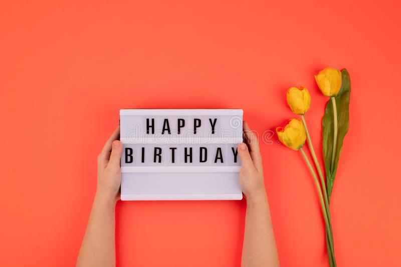 Happy birthday flat lay. Children hands holding light box with text Happy birthday and bouquet of yellow tulips on coral. Background, gift, present, pink, woman royalty free stock images
