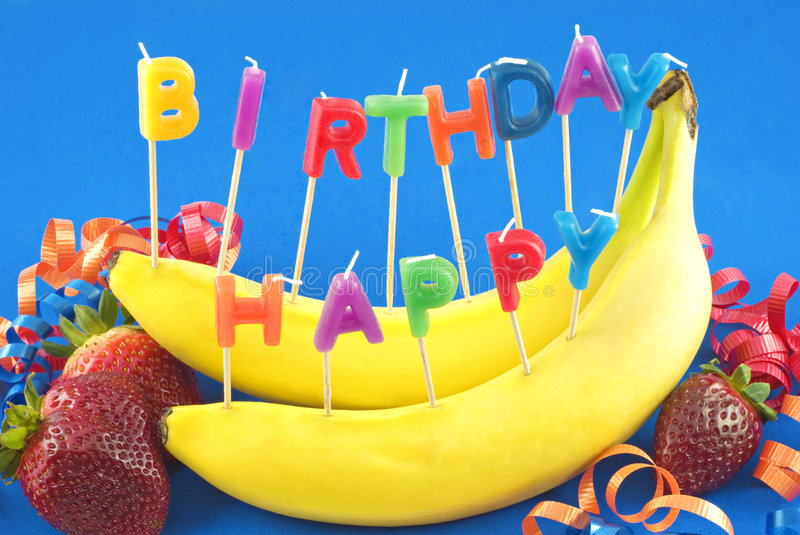 Happy Birthday Fruit. Candles spelling Happy Birthday stuck in bananas instead of cake for healthy lifestyle birthday, blue background with copy space stock photos