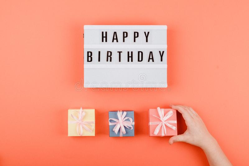 Happy birthday gift flat lay background. Children hands holding gift box with ribbon bow and light box with text Happy birthday on. Coral background, present royalty free stock photos
