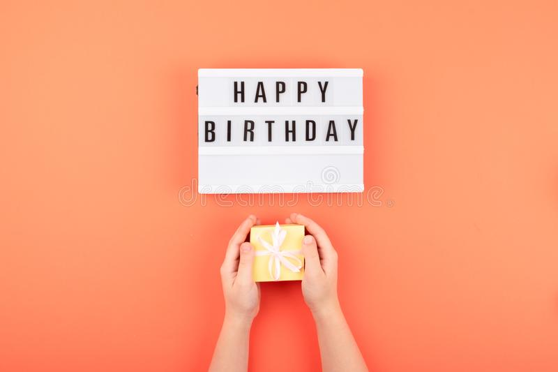 Happy birthday gift flat lay background. Children hands holding gift box with ribbon bow and light box with text Happy birthday on. Coral background, present royalty free stock photo