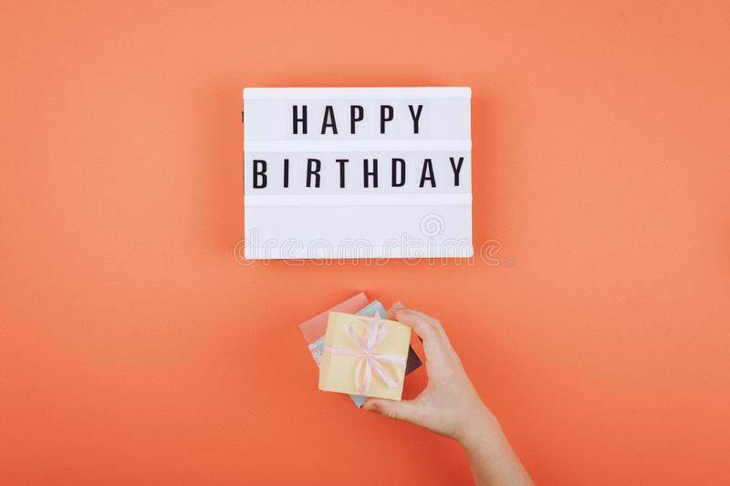 Happy birthday gift flat lay background. Children hands holding gift box with ribbon bow and light box with text Happy birthday on. Coral background, present royalty free stock images