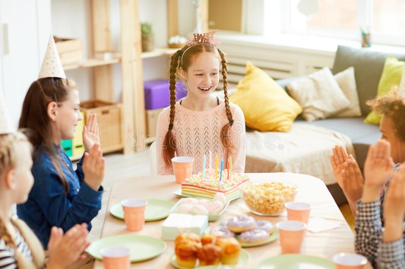 Happy Birthday Girl. High angle portrait of happy red-haired girl celebrating birthday with friends at party table, copy space stock photos