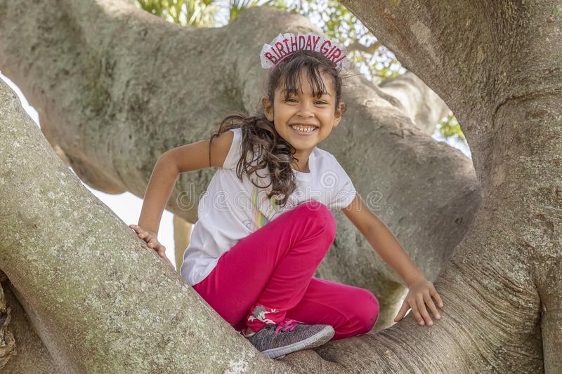 A happy birthday girl smiles from the top of the tree royalty free stock images