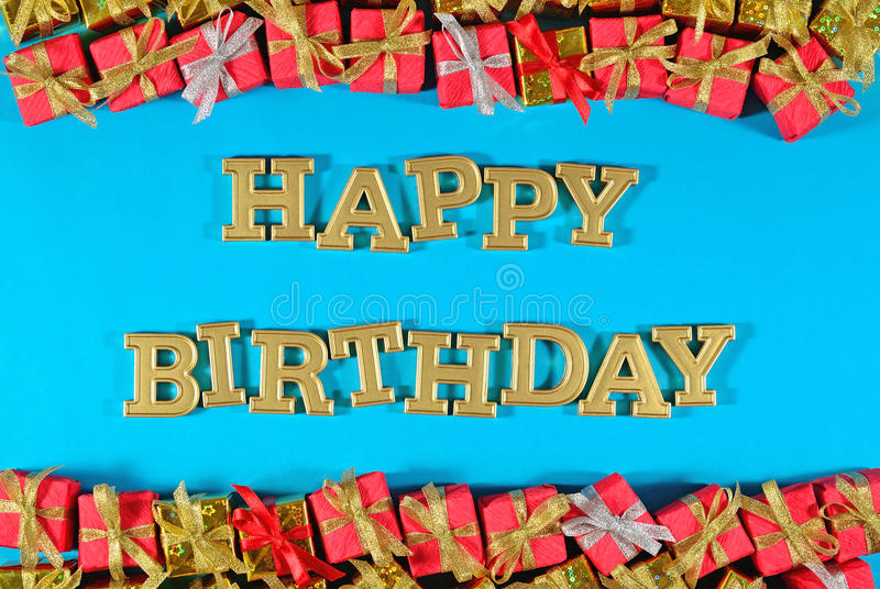 Happy birthday golden text and golden and red gifts on a blue. Background stock photography