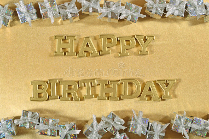 Happy birthday golden text and silver gifts. On a golden background royalty free stock image