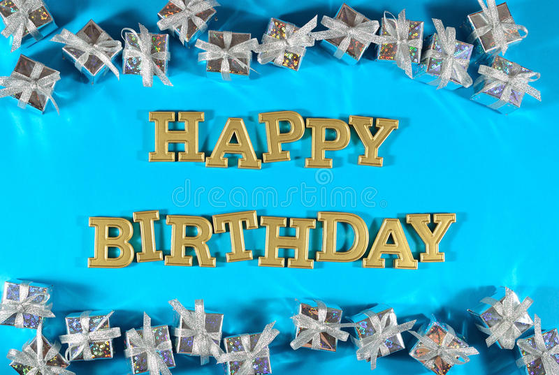 Happy birthday golden text and silver gifts on a blue. Background royalty free stock photo