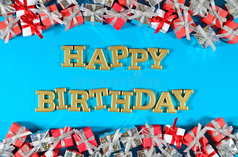 Happy birthday golden text and silver and red gifts on a blue. Background royalty free stock image