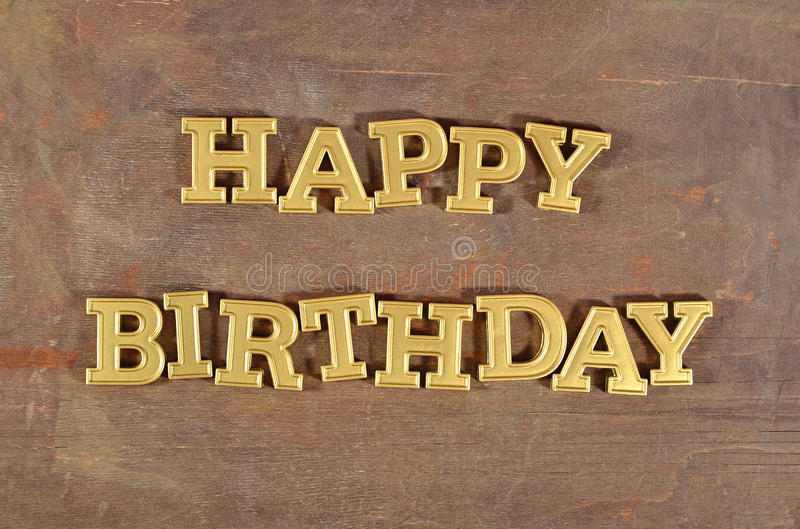 Happy birthday golden text. On a wooden background stock image