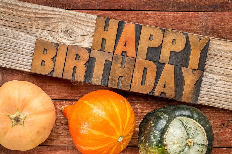 Happy Birthday greeting card. Text in letterpress wood type printing blocks over rustic grained barn wood with winter squash stock image