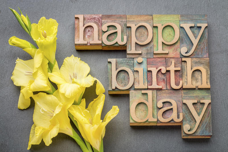 Happy birthday greeting card. Word abstract in letterpress wood type with a yellow gladiola flower against gray slate stone background royalty free stock images