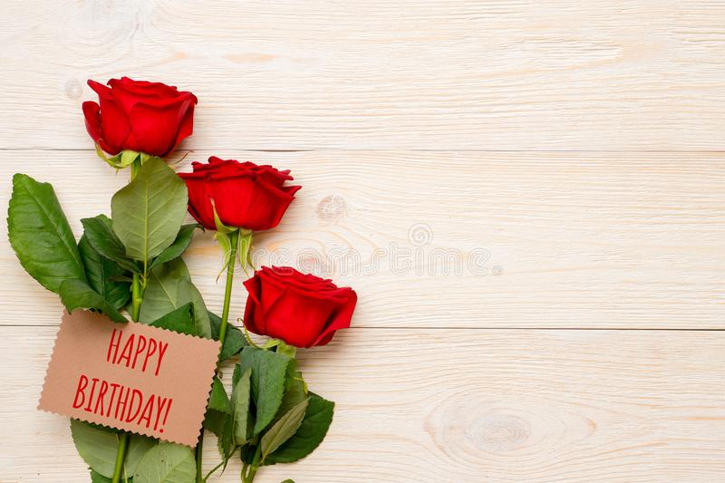Happy birthday greeting text on craft paper card. With red roses and copy space royalty free stock photos