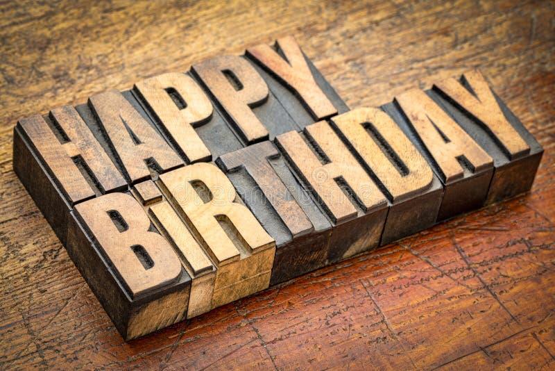 Happy Birthday greetings in letterpress wood type. Happy Birthday greeting card in vintage letterpress wood type against rustic weathered wood royalty free stock image