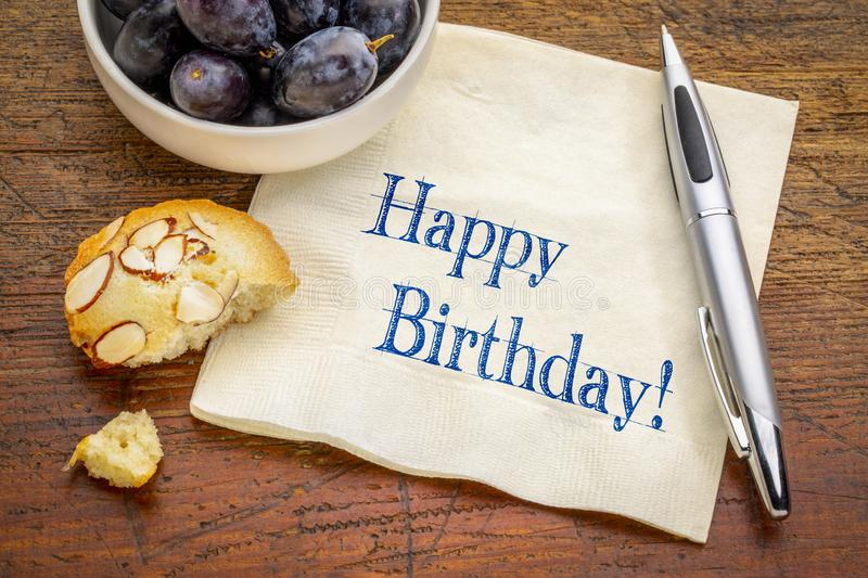 Happy Birthday greetings on napkin. Happy Birthday greeting - handwriting on a napkin with fresh grapes and a cookie royalty free stock photos