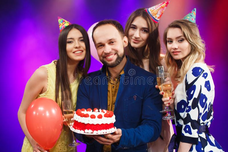 Happy birthday. Group of smiling friends gathered together with cake. stock images