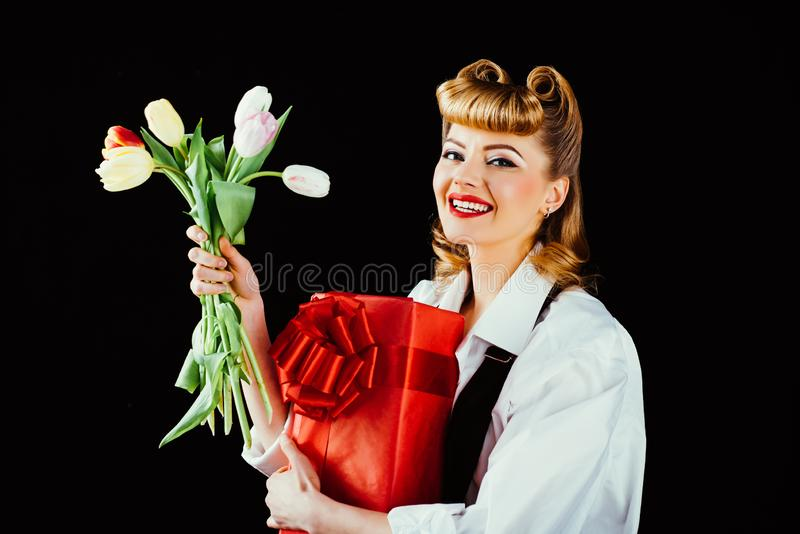 Happy birthday. Happy woman with present and flower. Girl with tulips and red surprise box on black background. Womens stock image