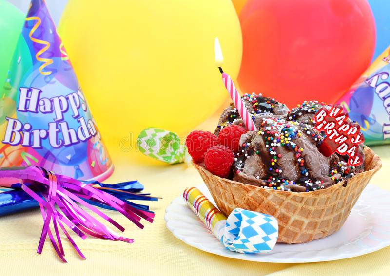 Happy Birthday Ice Cream. Large sugar wafer bowl of chocolate ice cream decorated for a Happy Birthday. Lit candle, balloons and party streamers stock photos