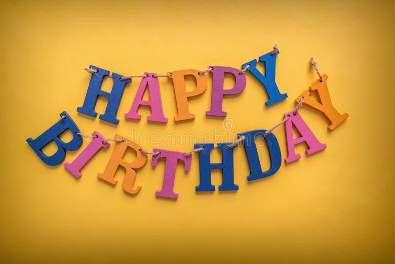 Happy birthday inscription. Happy birthday inscription on a yellow background royalty free stock image