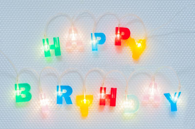 Happy birthday inscription. Multicolored glowing letters on white glossy background. Led volumetric lettering. Happy birthday inscription. Multicolored glowing royalty free stock photography