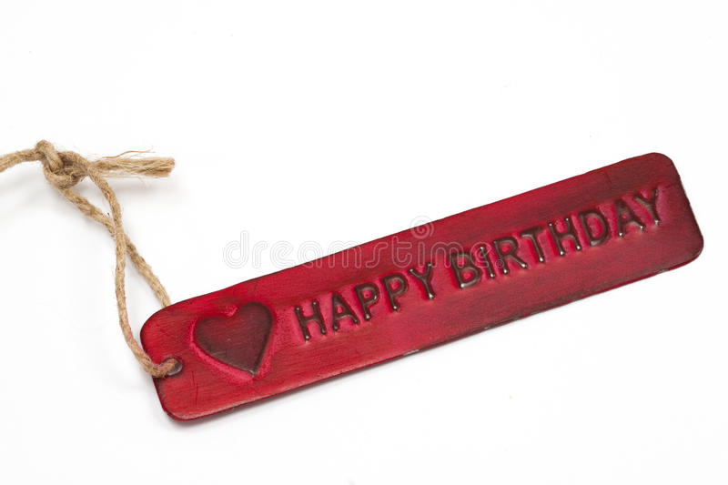 Happy Birthday Label. An old red metal label reading happy birthday on a white background with string cord stock photo