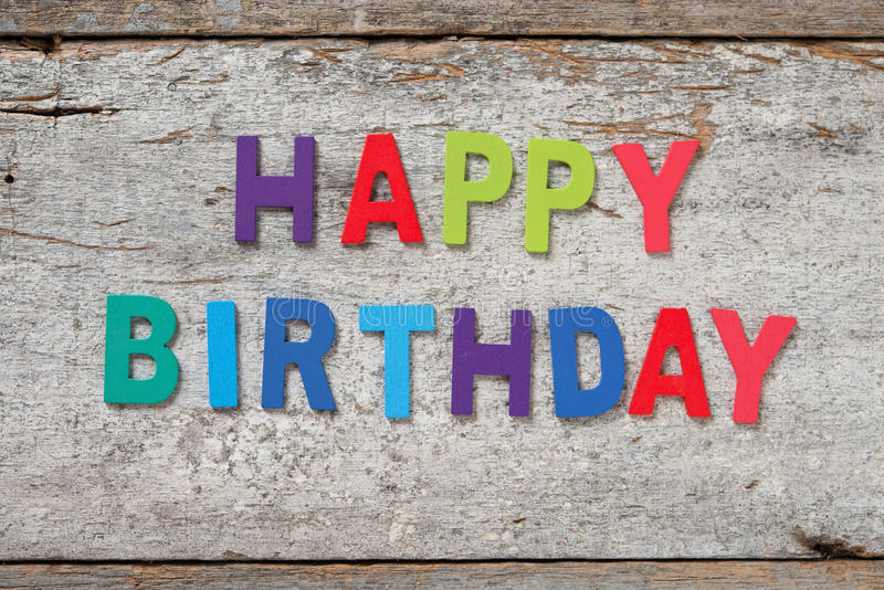 HAPPY BIRTHDAY letters. The colorful words HAPPY BIRTHDAY made with wooden letters on old wooden board royalty free stock image