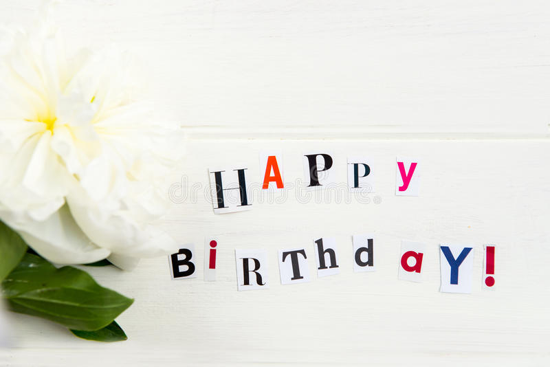 Happy Birthday Letters Cut out from Magazines and White Peonies stock photo