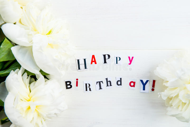 Happy Birthday Letters Cut out from Magazines and White Peonies royalty free stock image