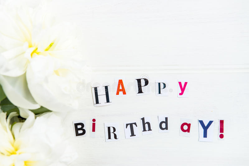Happy Birthday Letters Cut out from Magazines and White Peonies. Nearby, white background royalty free stock photography