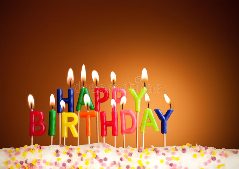 Happy birthday lit candles closeup. Happy birthday lit candles on brown background royalty free stock photo