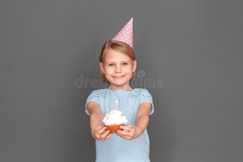 Happy birthday. Little girl wearing cap isolated on grey giving cupcake to camera smiling cheerful stock photography