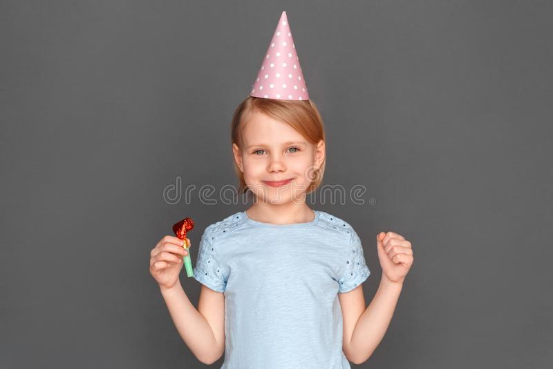 Happy birthday. Little girl wearing cap isolated on grey with party horn smiling stock image