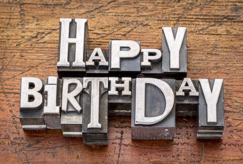 Happy Birthday in metal type. Happy Birthday greetings in vintage metal type printing blocks over grunge wood stock photo