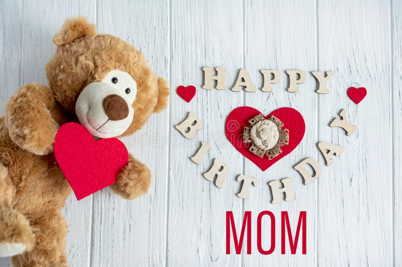 Happy birthday mom. Greeting card design for mom`s birthday with a teddy bear and a heart. Flat layout, top view. Happy mother`s. Happy birthday mom. Greeting royalty free stock photo