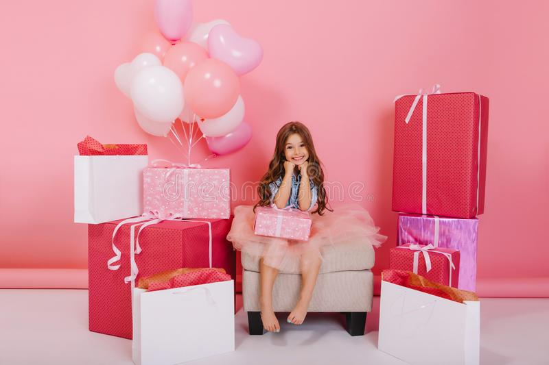Happy birthday mood of cute little girl in tulle skirt smiling to camera with present on pink background. Celebrating royalty free stock image